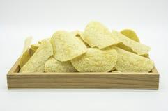 Microplaquetas de batata amarelas fritadas na bandeja de madeira isolada no fundo branco do arquivo com trajeto de grampeamento Imagem de Stock Royalty Free