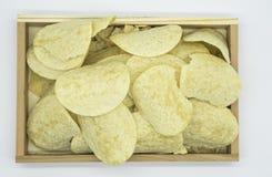 Microplaquetas de batata amarelas fritadas na bandeja de madeira isolada no fundo branco do arquivo com trajeto de grampeamento Imagens de Stock
