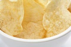 Microplaquetas de batata douradas deliciosas em uma bacia branca isolada no close-up branco do fundo fotos de stock