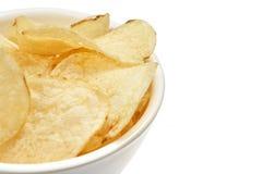 Microplaquetas de batata douradas deliciosas em uma bacia branca isolada no fundo branco fotografia de stock