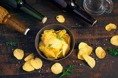 Microplaquetas de batata e cerveja em um fundo escuro, vista superior Imagens de Stock Royalty Free