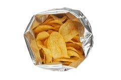 Microplaquetas de batata em um pacote de prata isolado em um close-up branco do fundo Fotos de Stock