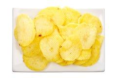 Microplaquetas de batata em um prato branco Fotografia de Stock Royalty Free