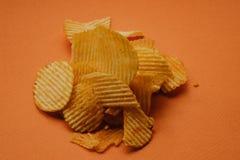 microplaquetas de batata fri?veis no fundo alaranjado Microplaquetas dos Nachos imagem de stock