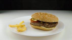 Microplaquetas de batata fritadas que caem para baixo no Hamburger, movimento lento, fast food, conceito da comida lixo video estoque