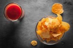 Microplaquetas de batata na bacia com suco de tomate no vidro Foto de Stock Royalty Free