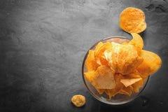 Microplaquetas de batata na bacia com suco de tomate no vidro Imagens de Stock