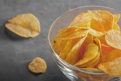 Microplaquetas de batata na bacia com um suco de tomate no vidro Fotos de Stock