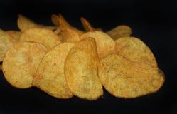 Microplaquetas de batatas amarelas no fundo - petisco popular fotografia de stock royalty free