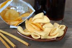 Microplaquetas de milho da batata frita de batata do petisco No assoalho de madeira velho Foto de Stock