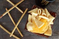 Microplaquetas de milho da batata frita de batata do petisco No assoalho de madeira velho Imagens de Stock