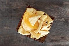 Microplaquetas de milho da batata frita de batata do petisco No assoalho de madeira velho Fotografia de Stock Royalty Free
