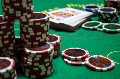 Microplaquetas de pôquer com cartões de jogo em uma tabela verde Foto de Stock