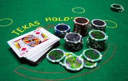 Microplaquetas de pôquer com cartões de jogo em uma tabela verde Imagens de Stock Royalty Free