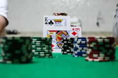 Microplaquetas de pôquer com cartões de jogo em uma tabela verde Fotografia de Stock Royalty Free