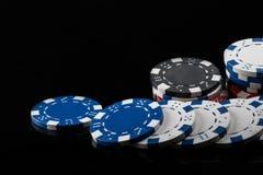 Microplaquetas de pôquer de cores diferentes, dispersadas de comprimento em uma superfície reflexiva preta Fotos de Stock