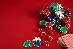 Microplaquetas de pôquer e plataforma de cartão no fundo vermelho Grupo de microplaquetas de pôquer diferentes Fundo do casino Imagens de Stock Royalty Free