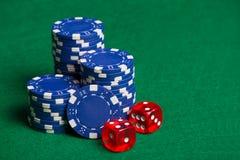 Microplaquetas de pôquer azuis e cubos vermelhos na tabela verde Fotografia de Stock Royalty Free