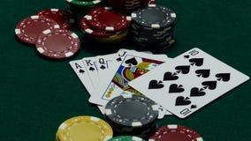 Microplaquetas do casino e cartões do pôquer na tabela verde filme