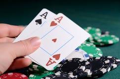 Microplaquetas do casino e pares de áss na mão de uma mulher Conceito do jogo de pôquer Imagem de Stock Royalty Free
