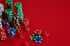 Microplaquetas do póquer no fundo vermelho Grupo de microplaquetas de pôquer diferentes Fundo do casino Foto de Stock
