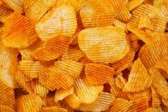 Microplaquetas douradas onduladas do fundo com textura Textura do alimento Microplaquetas de batata Vista superior Zombaria acima foto de stock royalty free