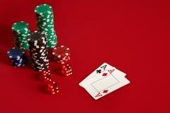 Microplaquetas e áss de pôquer no fundo vermelho Grupo de microplaquetas de pôquer diferentes Fundo do casino Foto de Stock Royalty Free