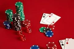 Microplaquetas e áss de pôquer no fundo vermelho Grupo de microplaquetas de pôquer diferentes Fundo do casino Imagens de Stock