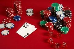 Microplaquetas e áss de pôquer no fundo vermelho Grupo de microplaquetas de pôquer diferentes Fundo do casino Foto de Stock