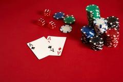 Microplaquetas e áss de pôquer no fundo vermelho Grupo de microplaquetas de pôquer diferentes Fundo do casino Imagem de Stock