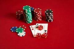 Microplaquetas e áss de pôquer no fundo vermelho Grupo de microplaquetas de pôquer diferentes Fundo do casino Fotografia de Stock Royalty Free