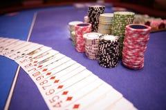 Microplaquetas e cartões do casino que encontram-se na tabela Imagem de Stock