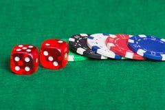 Microplaquetas e dados coloridos de pôquer em um feltro verde Imagem de Stock