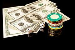 Microplaquetas e dados de pôquer com americano cem dólares de contas no fundo preto Fotografia de Stock
