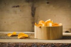 Microplaquetas em uma bacia de madeira na tabela Fotografia de Stock Royalty Free
