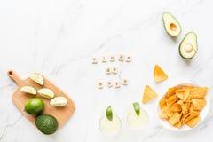 Microplaquetas frescas do abacate, do cal, da bebida e do nacho que encontram-se no fundo de m?rmore Receita para o partido de Ci foto de stock royalty free