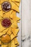 Microplaquetas mexicanas do nacho e mergulho colorido nas bacias de vidro no fundo de madeira branco, vista superior, beira verti Foto de Stock