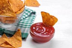 microplaquetas Nachos em uma bacia com molho vermelho em uma tabela de madeira branca snacks foto de stock royalty free