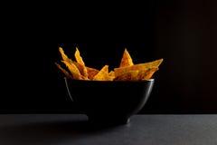 Microplaquetas picantes fritadas do lavash na terrina preta fotografia de stock royalty free