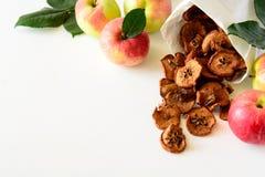 Microplaquetas saborosos da maçã envolvidas no papel no fundo de madeira branco Fotos de Stock