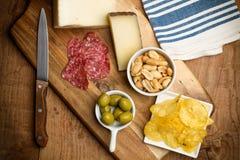 Microplaquetas, salsicha, queijo, azeitonas em uma tabela de madeira Imagem de Stock Royalty Free