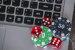 Microprocesadores de juego y dados rojos en fondo del teclado del ordenador portátil Imágenes de archivo libres de regalías
