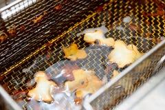 Microprocesadores de la manzana de la tierra que son cocinados en aceite Foto de archivo