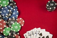 Microprocesadores y tarjeta de juego para el póker en fondo del fieltro del rojo Imagen de archivo libre de regalías