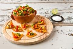 Microprocesadores y verduras de los Nachos en un cuenco y un tequila de la loza de barro Fotografía de archivo