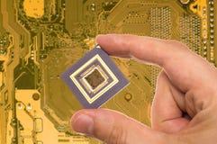 Microprocessor in hand  over PCB Stock Photo
