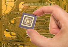 Microprocessor in hand  over PCB Royalty Free Stock Images