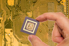 Microprocessor in hand  over PCB Royalty Free Stock Photos