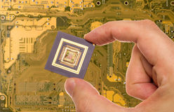 Microprocessor in hand  over PCB Royalty Free Stock Photo
