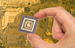 Microprocessor in hand  over PCB Royalty Free Stock Photography